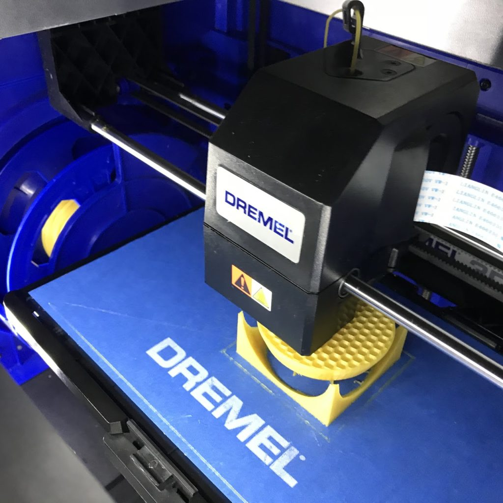 Dremel 3D Printer printing a yellow ball in a box.