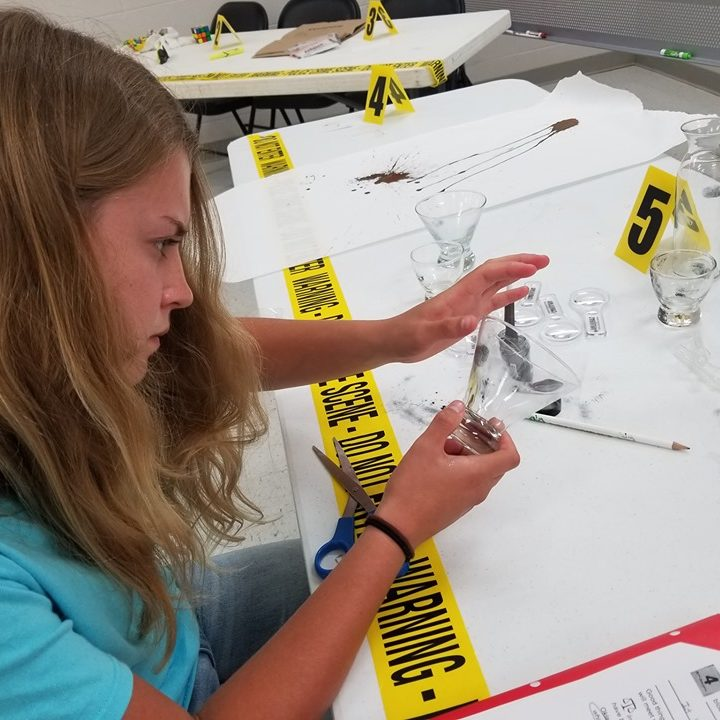 youth taking fingerprints from glass