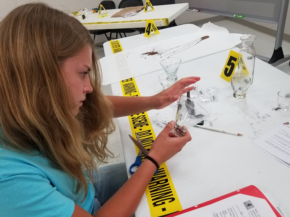 student sitting at a table examining crime scene equipment.