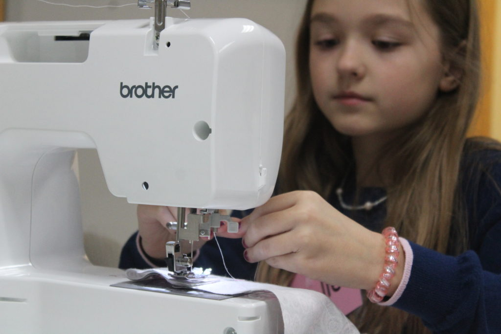 young girl sitting behind a sewing machine threading the needle.