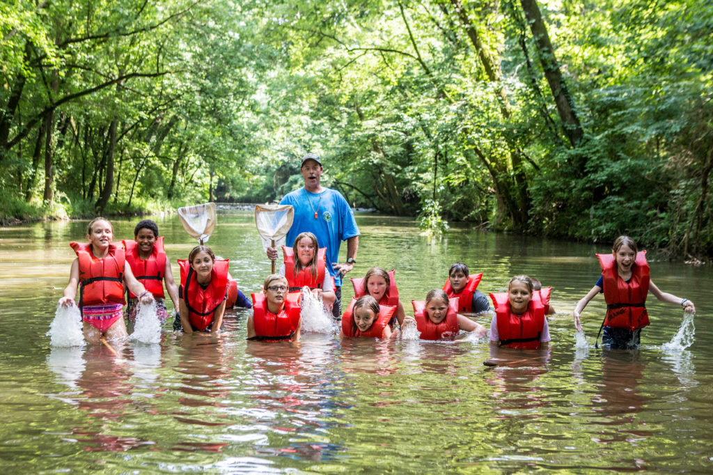 youth splashing in the river at 4-H Camp wearing life vests.