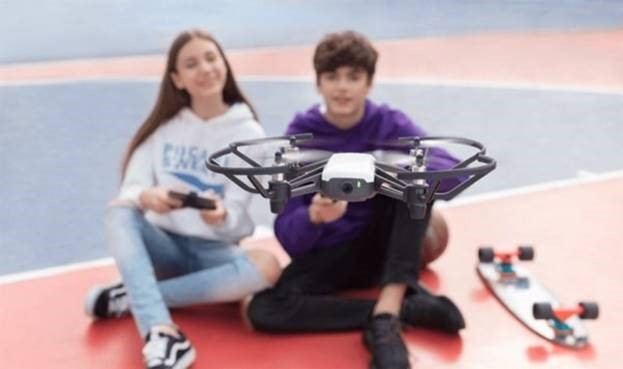 teen girl and boy flying a drone
